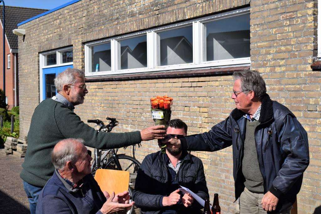 Bestuurslid Jan Heeres reikt de overwinningsbloemen in de open lucht uit aan Dirk Buwalda.(Foto: P. Broekhuizen)
