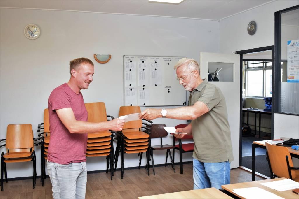 Voorzitter en vluchtwinnaar Jan Heeres reikt alsnog de prijzen uit aan Reimer Strikwerda.