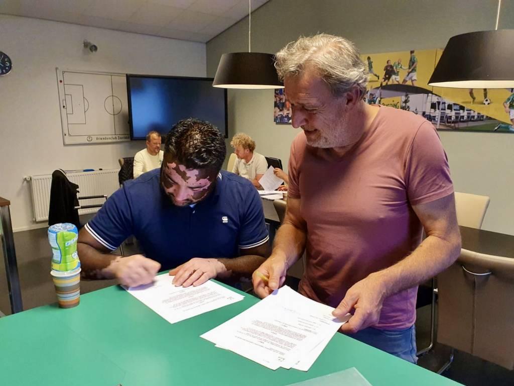 Onder toeziend oog van bestuurslid Henk Zegel tekent Camaru van Oostveen zijn contract voor het seizoen 2020-2021.