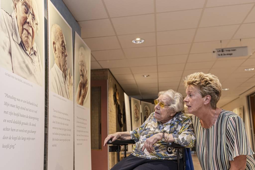 Mevrouw Vos-van Ingen bij haar portretfoto van de expositie 'Noorderbreedte viert de vrijheid' in De Spiker.